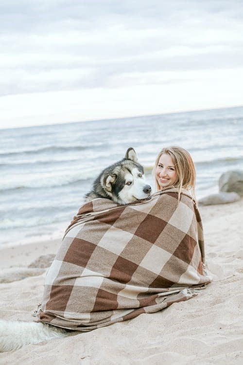 A proud dog owner having a great time with her puppy.